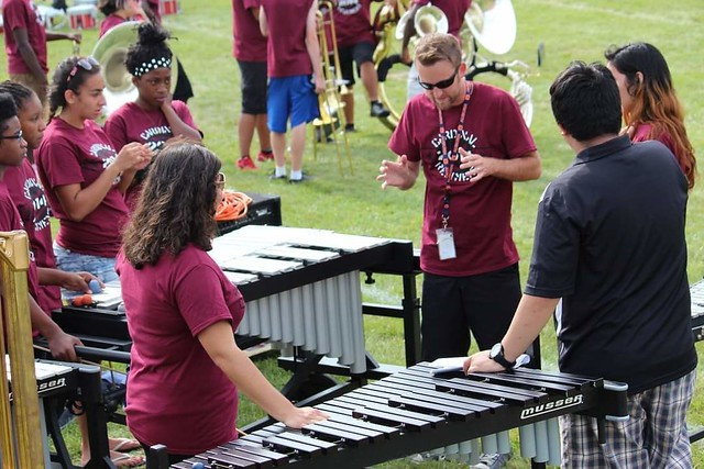 Justin Antos talks with band students.
