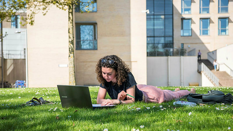 A female student lying on the grass using her laptop