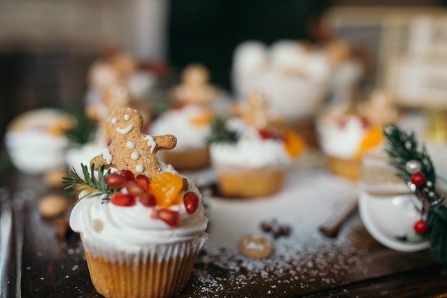Cupcake with whipped cream decorated with fruits and a cookie.