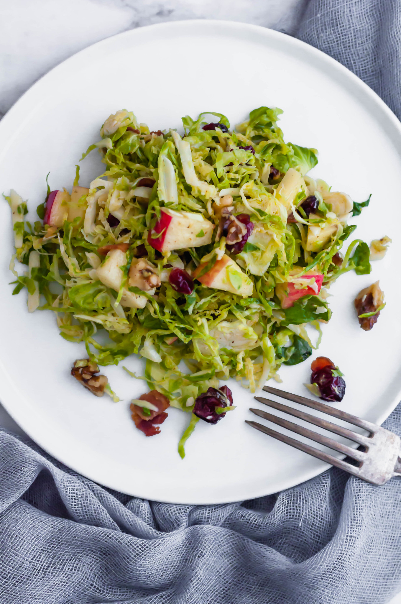 This Shaved Brussels Sprouts Salad is the perfect addition to your Thanksgiving table. It's bringing all the fresh fall vibes. Full of fresh shaved brussels sprouts, honeycrisp apples, craisins, sharp cheddar cheese, toasted walnuts and the most delicious honey mustard vinaigrette. Prepare the ingredients ahead of time and toss together at the last minute for a stress free holiday dinner.