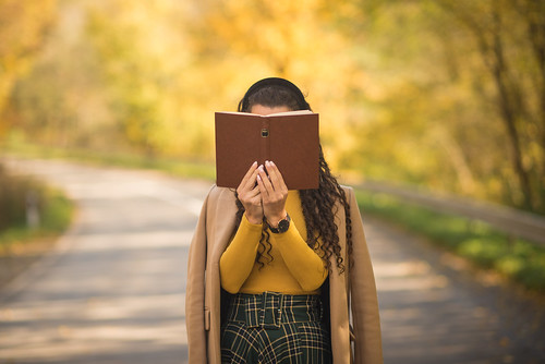 Woman with curly hair standing on the road and covering her face with a book. | by shixart1985