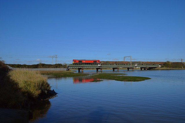Red Shed 66034 pulls away from a signal check as it crosses the River Stour at Cattawade, with 6V07 12.07 to Neasden from Ipswich Griffin Wharf sand train. 04 11 2020