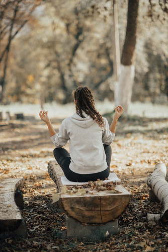 Woman meditation on a log in a park. | by shixart1985