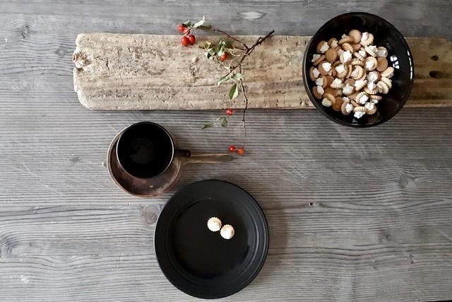 Kleine koekjes in zwarte kom houten snijplank