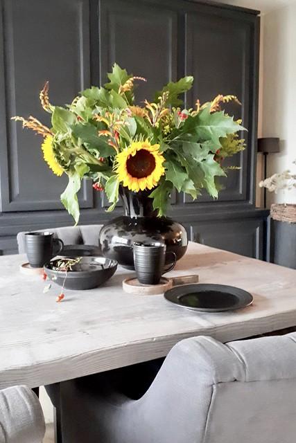 Zwarte vaas met zonnebloemen landelijke eethoek