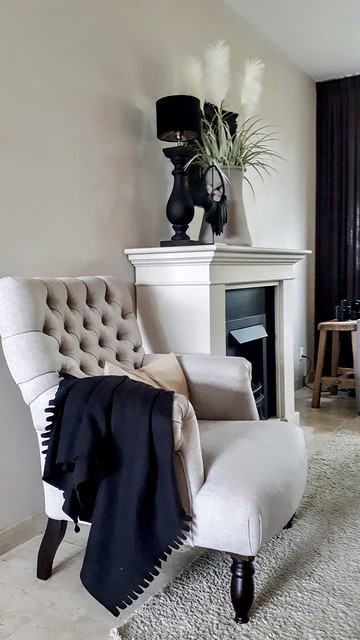 Beige gecapitonneerde fauteuil zwarte plaid