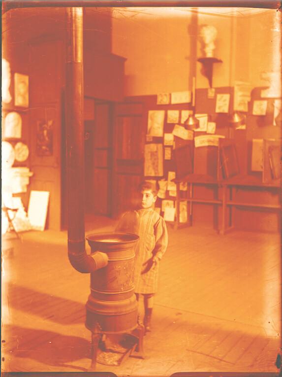 Niño junto a una estufa en una clase de la Escuela de Artes a comienzos del siglo XX, foto de Pedro Román Martínez. Fondo Rodríguez, Archivo Histórico Provincial de Toledo, JCCM, signatura R-138-3