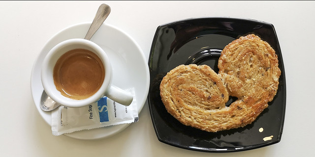Photograph of a cup of coffee and a pastry