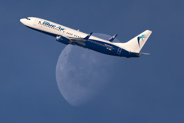 Blue Air 737 banking in front of the moon