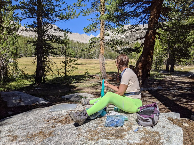 Vicki doing laundry on a boulder in Crabtree Meadow with a view of Mount Whitney