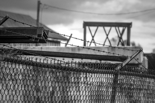 urbanlandscape urbandecay metalfence barbedwire architecturalforms dusk asheville northcarolina nikond3300 mamiyasekkor145mmf4 mamiyaprime primelens monochrome monochromatic blackandwhite digital