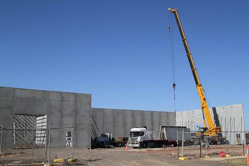 Crane at work erecting a tilt slab concrete warehouse in the industrial estates of Truganina