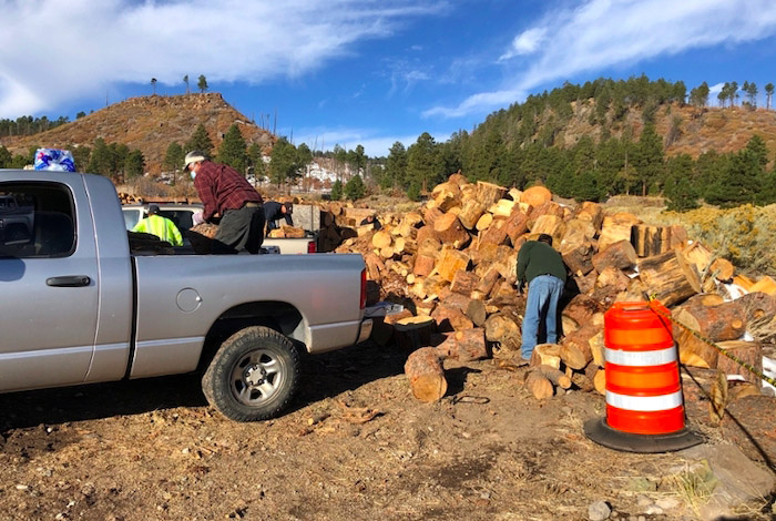 Tribal members of the San Ildefonso Pueblo load firewood into their trucks on October 30, 2020.