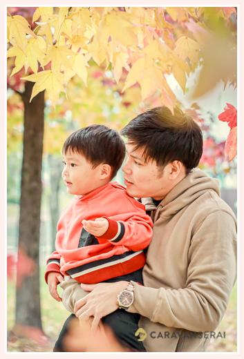 カエデの木の下の親子(パパと男の子)