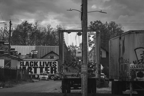 urbanlandscape abandonedtrailers trailers blacklivesmatter dusk riverdistrict asheville northcarolina nikond3300 mamiyasekkor145mmf4 primelens nikonprime blackandwhite monochrome monochromatic digital