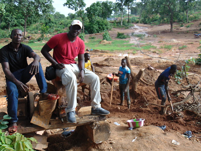 Ibrahima sitting on a crusher with miners in from Burkina Faso in Setiya, Guinea