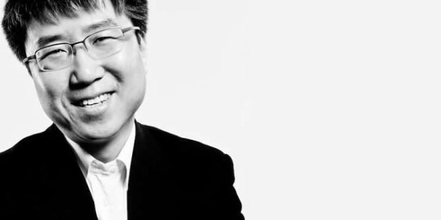 A potrait of Ha-Joon Chang, in a suit jacket, smiling