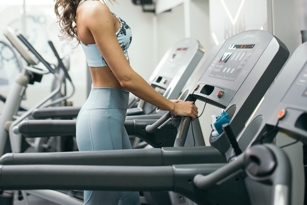 Young blonde woman running on a treadmill in the gym closeup.