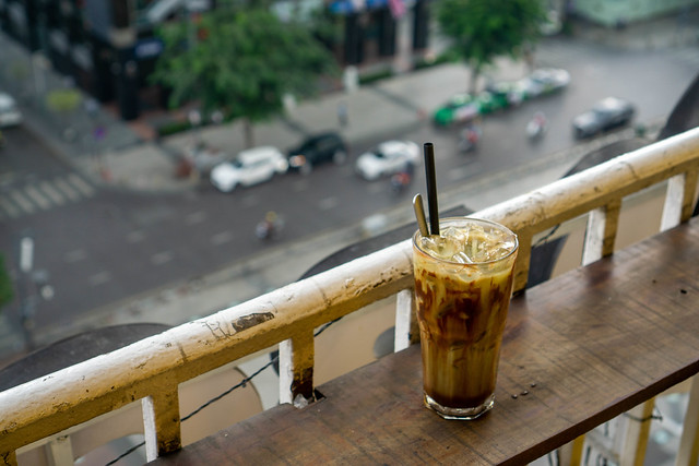 Bokeh Photo of Cold Chocolate Drink with Plastic Straw and Spoon on a Balcony of a Coffee Shop looking down on the Streets