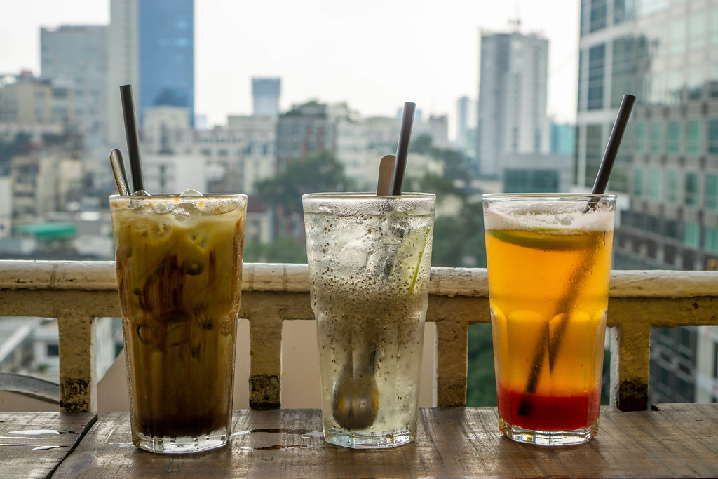 Three different Cold Drinks with Plastic Straws on a Balcony with a View of Ho Chi Minh City, Vietnam in the Background