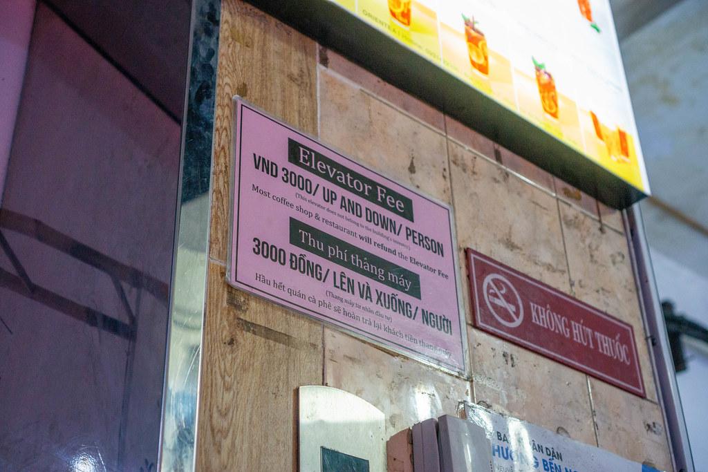 Elevator Fee Sign Board next to a No Smoking Sign inside The Cafe Apartment Building in Saigon, Vietnam