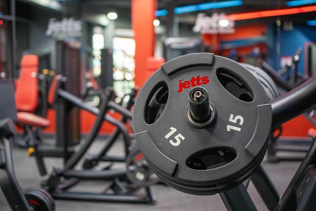 Mehrere Gewichtsscheiben auf einer Latzug Maschine in einem modernen Fitnessstudio Nahaufnahme