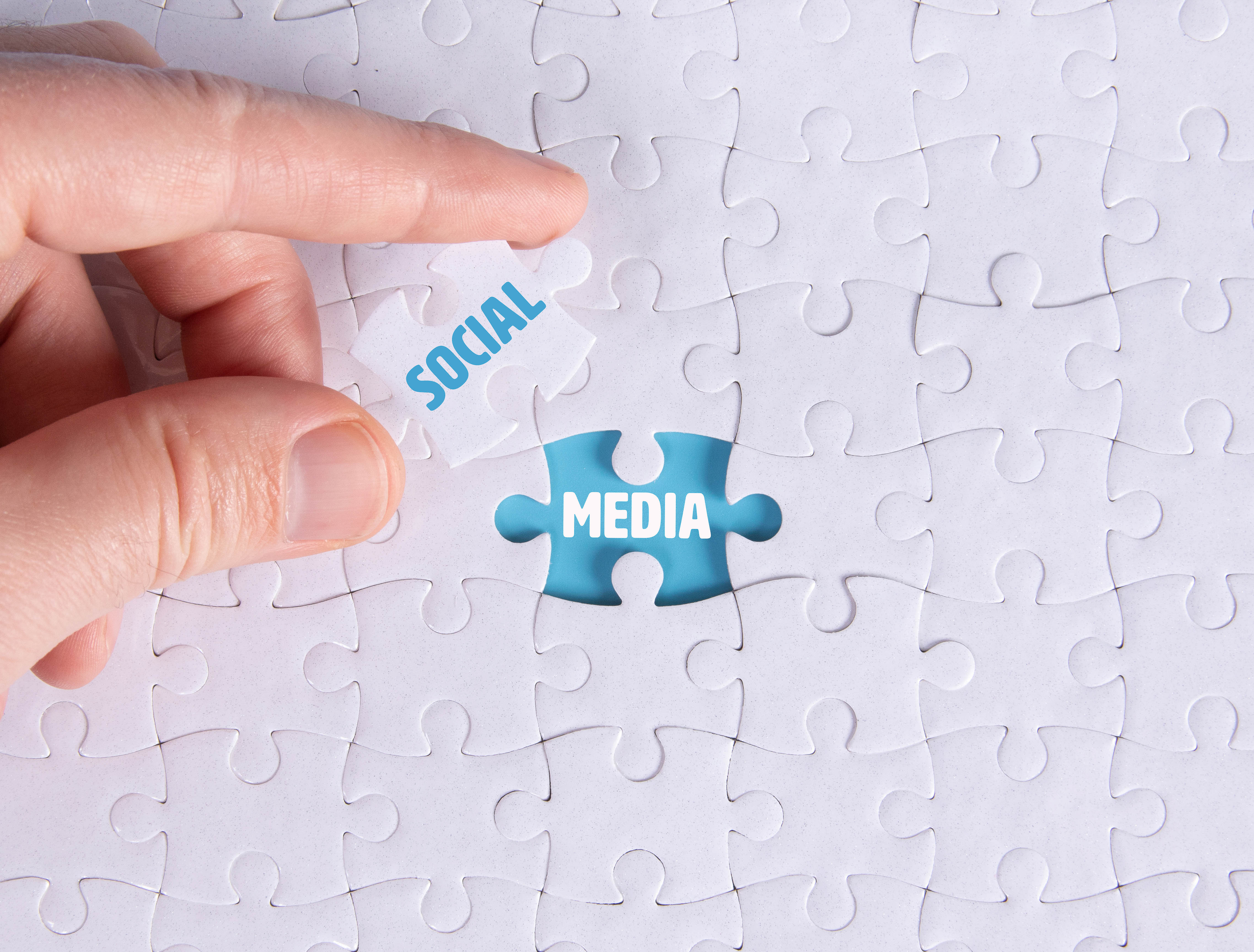 Hand holding piece of jigsaw puzzle with word social & media