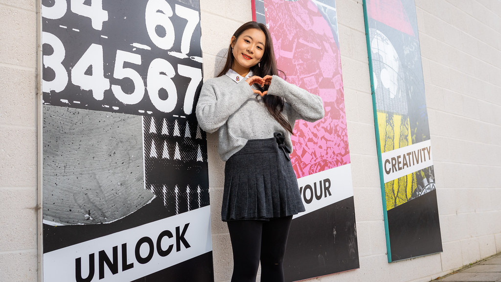 Tiffany posing in front of a creativity mural.