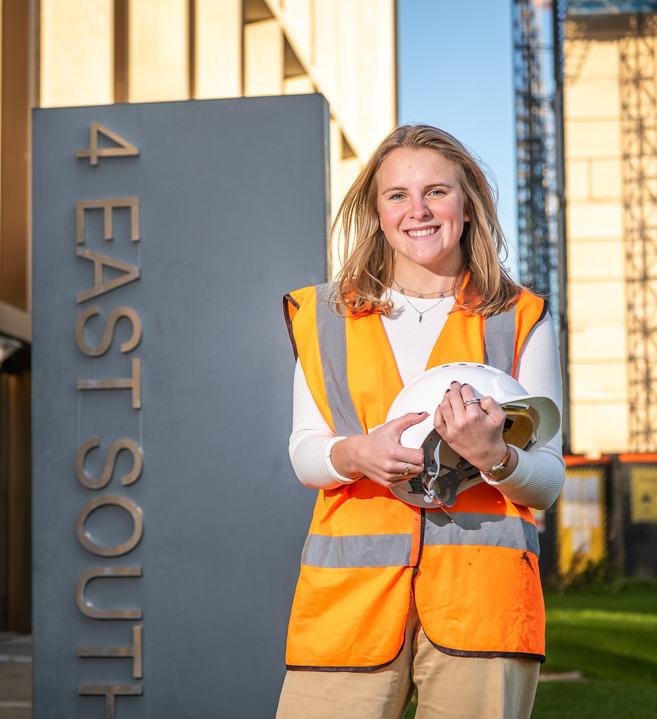 Molly wearing a high vis jacket standing beside the 4 East South building on campus.