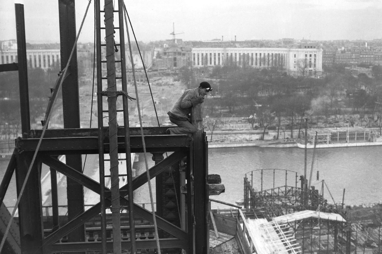 08. 1936. Рабочий сидит на вершине опоры башни во время модернизации первого этажа Эйфелевой башни для Всемирной выставки 1937 года, 14 декабря