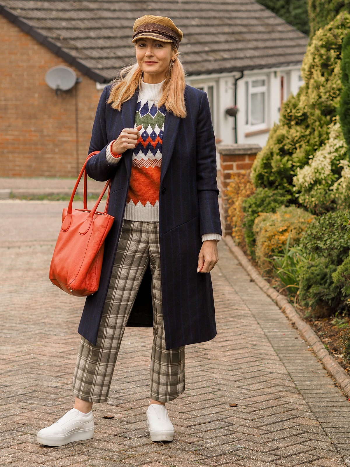 Styling a Classic Tailored Coat With Bold Winter Patterns (navy pinstripe coat, orange, green and white Nordic patterned sweater, green check trousers, orange tote bag, white chunky trainers, camel baker boy hat) | Not Dressed As Lamb, Over 40 Fashion