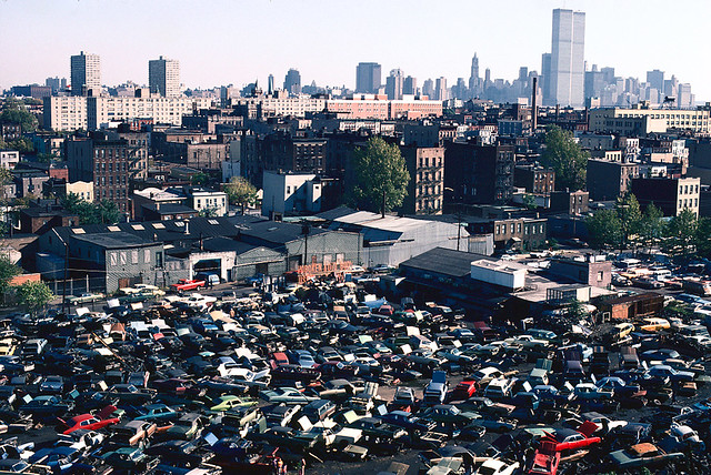 A pile of colorful junked cars lays scattered in the Hoboken Auto Body lot as seen from the Jersey City Heights near Observer Highway. Lower Manhattan and the World Trade Center hover in the background. Sept 1978