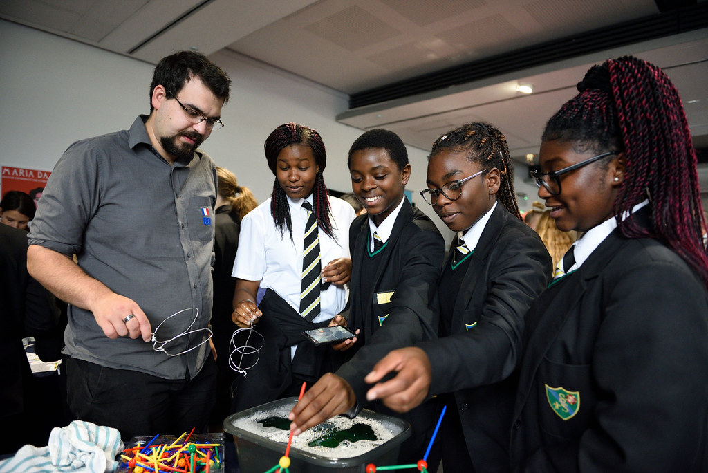 A researcher explaining a science demonstration to three school students