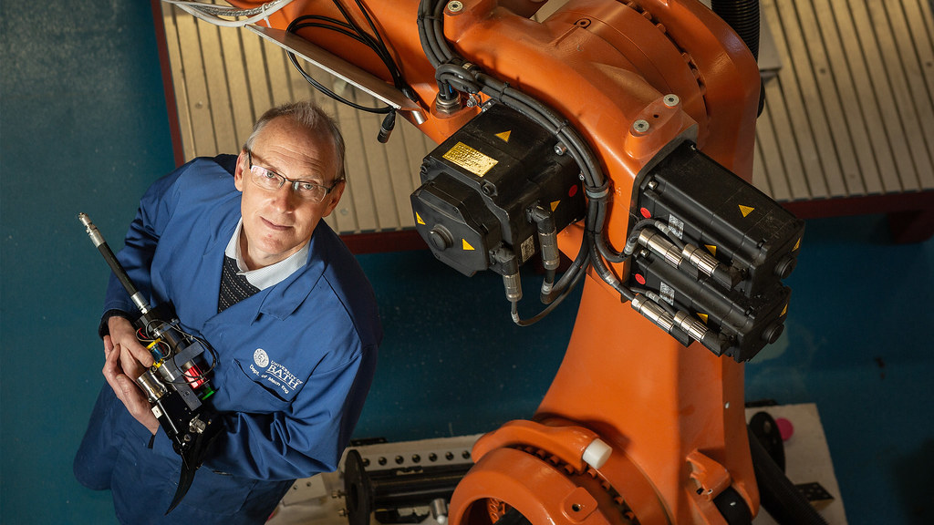 Professor Andrew Plummer holds a hydraulic ankle prototype next to a robotic arm.