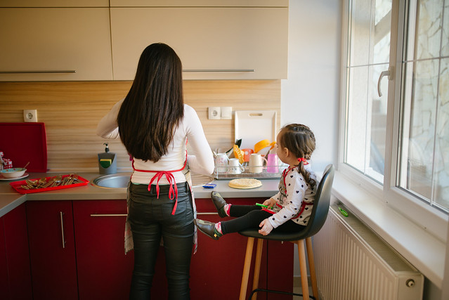 Mother and daughter in the kitchen. Back view.