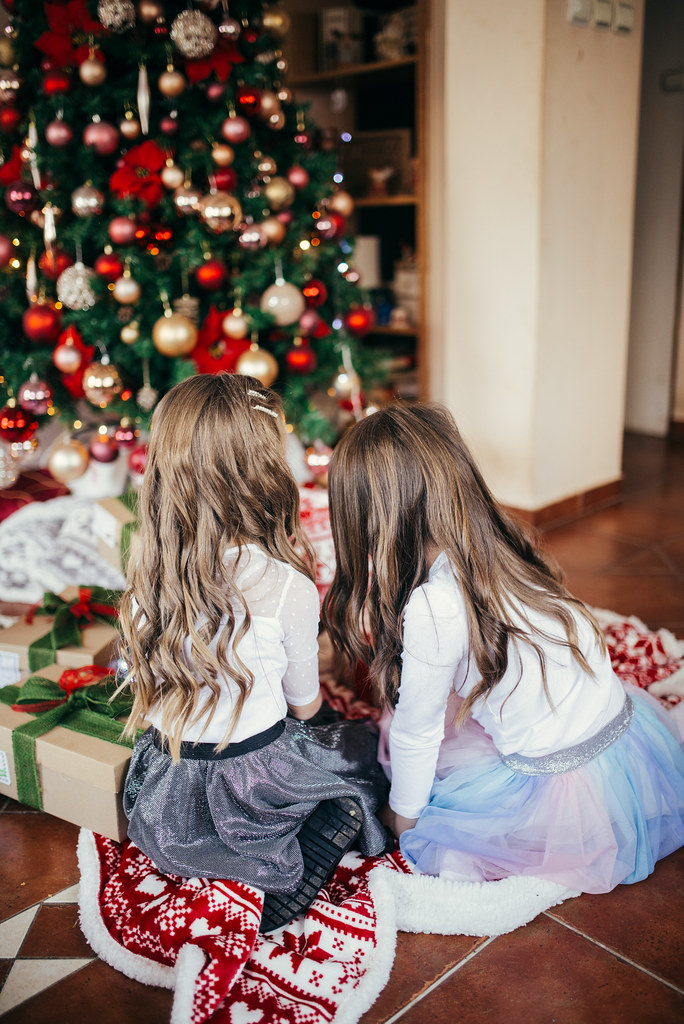 Two little girls sitting near Christmas tree. Back view.