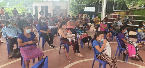 Workers sit, socially distanced, at a meeting with their union to receive material support following the devastation of their neighborhood, Nejapa, in El Salvador