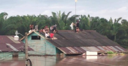 People standing on top of a roof to escape extremely high floodwaters in Honduras.