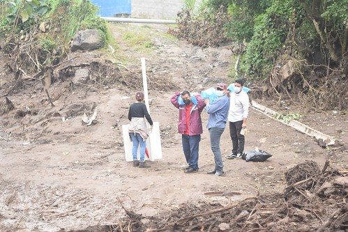 Workers carrying supplies in an area devastated by a landslide in Nejapa, El Salvador
