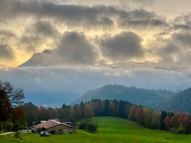 Autumn mist and Zahmer Kaiser mountain range in the clouds seen from Breitenau near Kiefersfelden in Bavaria, Germany