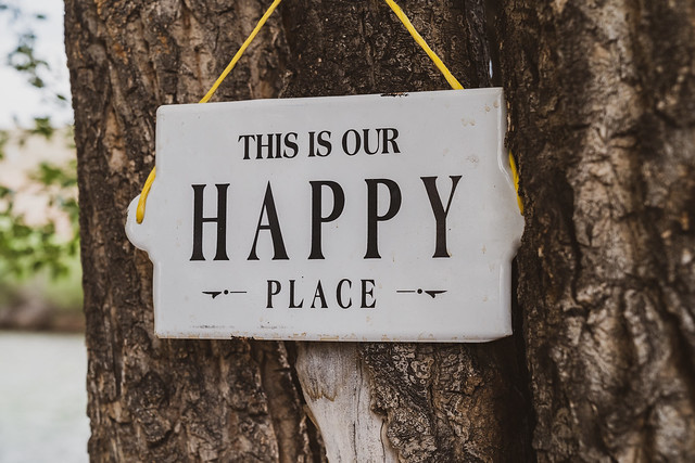 Outdoor sign hung on a tree reading, This is our happy place