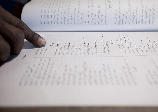 Forefinger of a witchdoctor reading jinn book, Lamu County, Lamu, Kenya