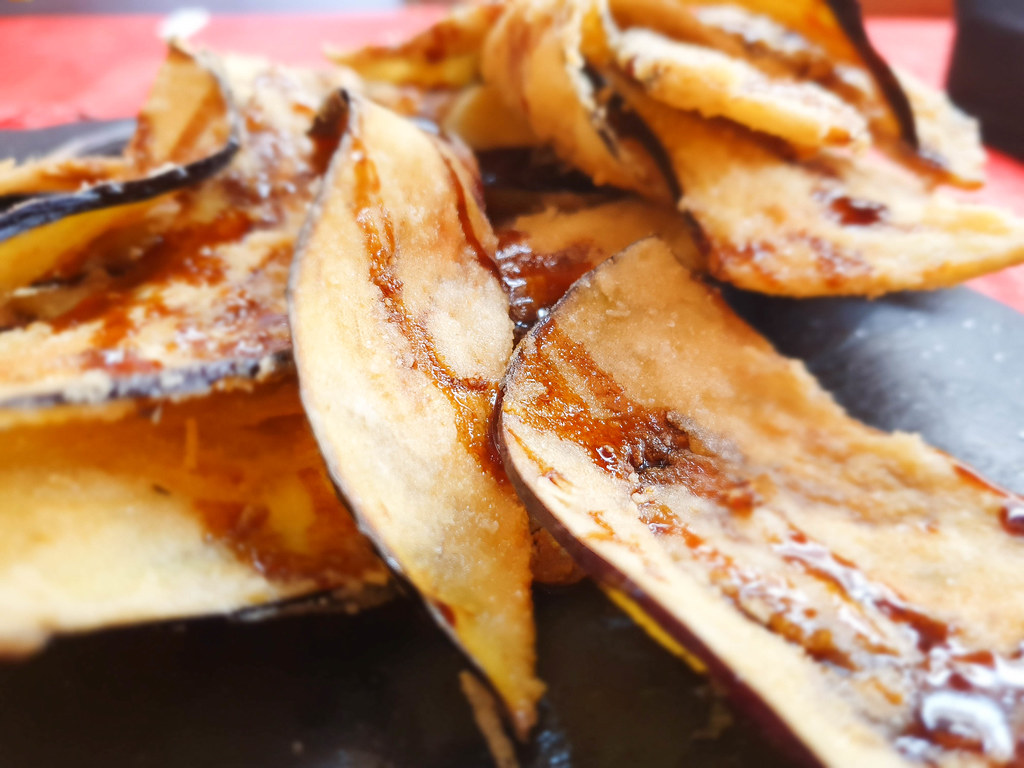 A close-up of crispy slices of fried aubergines drizzled with dark brown cane honey