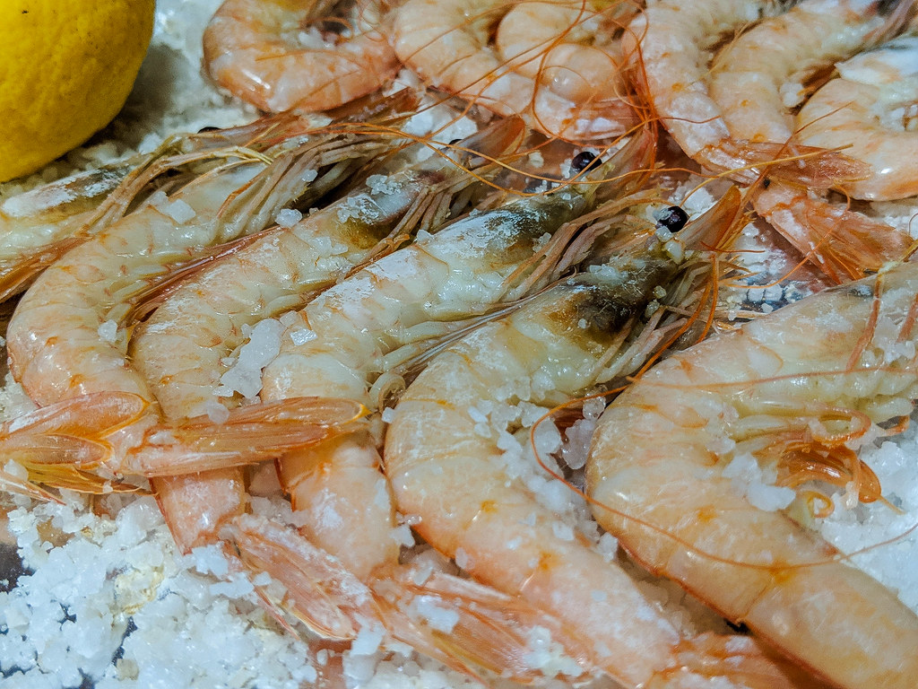 A close-up of a plate of giant prawns served whole on a bed of white coarse salt