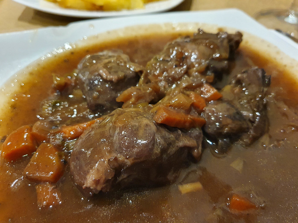 tender pieces of pork cheek in a sea of brown sauce, with pieces of orange carrot on the plate