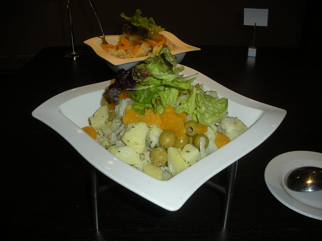 A square plate with potatoes at the bottom, topped with yellow slices of oranges and green olives. On top, there are a couple of leafs of green salad