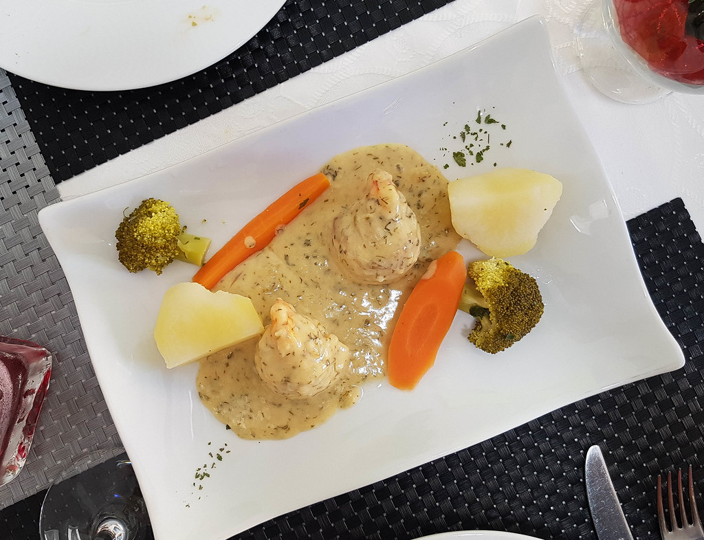 The photo was taken from above. In the middle of the table there is a white rectangular plate on which there are two meatballs covered by a very light brown sauce. Around them there are 2 long slices of carrots, two pieces of yellow potato and two green florets of broccoli. The plate stands on a black and gray table cover.