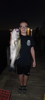 Photo of boy holding a striped bass