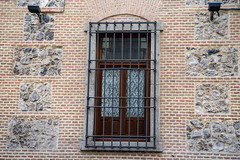 Interesting window and  wall brick facade with bars on window in Madrid Spain