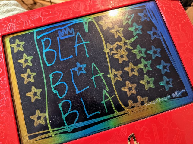 Etch-a-Sketch with column of three Bla words, framed and with stars and one crown stamped for decoration by a child